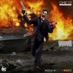 Mezco Toyz One:12 Collective Joker Action Figure, posed against an explosion